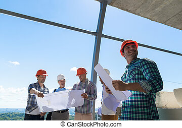 Group Of Builders In Hardhat Hold Plan Discussing Project On...