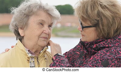 Woman soothes old woman during stress outdoors - Adult woman...