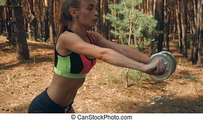 Slim strong athletic girl stands and lifts a dumbbell in...