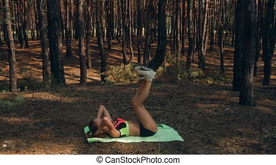 young slender sexy girl lies on her back and shakes press in...