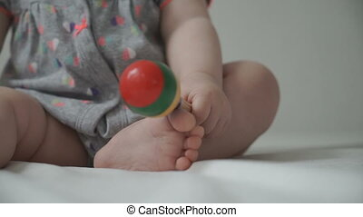 A baby child plays with a rattle