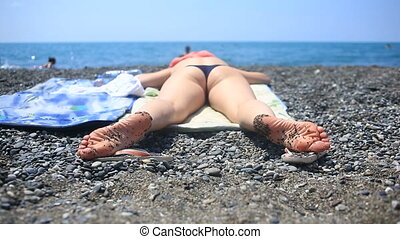 Woman sunbathing on the beach lying on stones.
