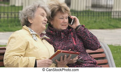 Two women sit and discuss about nature outdoors