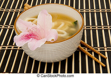 Miso soup with noodles garnished with a pink flour Focus is...