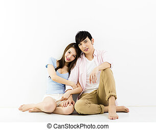 Portrait Of Happy Young Couple Sitting On Floor