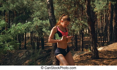 sport girl with elastic tummy stands in the Woods and looks...