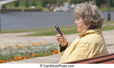 Mature old woman talking on smartphone outdoors