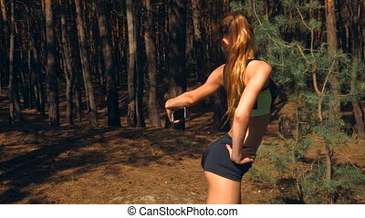 beautiful athlete stands in the forest and takes pictures of...