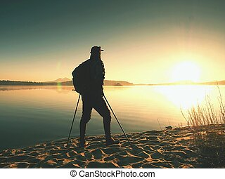 Older man tourist standing close to water on empty beautiful...