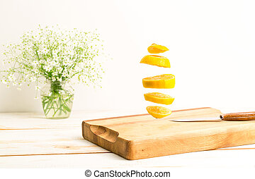 Sliced whole lemon flying above a wooden chopping board with...