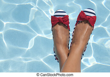 A woman sports some nautical shoes with a pool on a sunny...