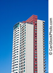 Red and White Condo Tower on Blue Sky