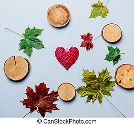 Autumn leaves and heart shape gift on white background