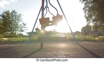 A swing on chains without people lingering alone in an empty...