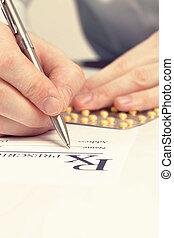 Medical doctor filling out drug prescription - studio shot