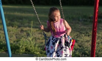 Seven year old cheerful girl in a pink dress swinging on a...