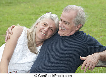 A senior citizen man looks happily at his wife on a casual afternoon.
