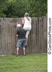 Her husband helps her peek over the fence to see what the...