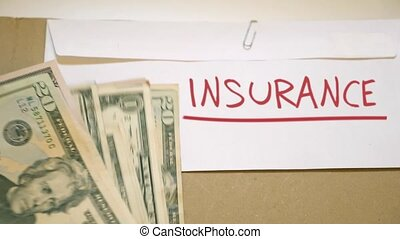 INSURANCE costs concept - USD bills on INSURANCE cash...