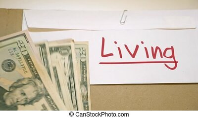 Living costs concept - USD bills on Living cash envelope