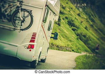 Camper Van on the Road. Class C Motorhome Coach with Bikes...