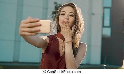 Sending Kiss by Smartphone - Sexy brunette girl sending kiss...