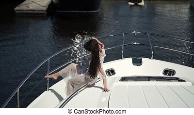 Unrecognizable young woman sitting on yacht at sunny day