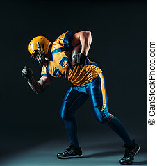 American football offensive player with ball in hand,...