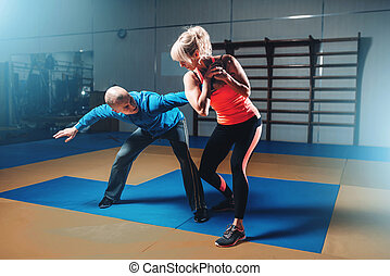 Woman in actoin on self-defense training with personal...