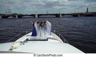 Bride and bridesmaids on yacht at sunny day