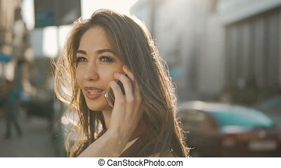 Woman Talking by Phone - Sunset shot of attractive brunette...