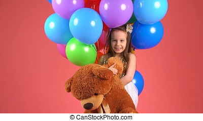 Portrait of a little girl with a toy bear. The child holding soft toy in hands, laughing and smiling
