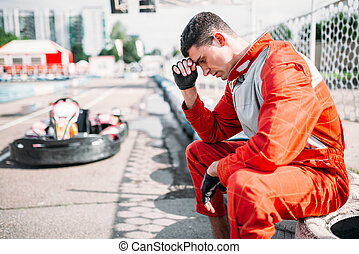 Karting racer sits on a tire, outdoor kart track. Motor...