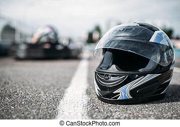 Racer helmet on asphalt, karting sport concept - Racer...