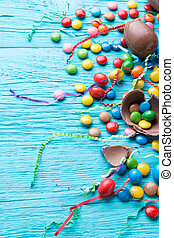 Multicolored dragees, chocolate eggs, ribbons on blue wooden...
