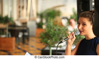 Girl singer sings into a microphone in a seaside restaurant...