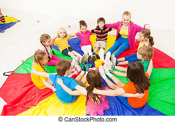 Happy children playing circle games with teacher