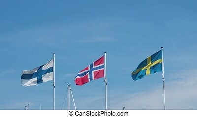Three flags waving - Three Scandinavian flags waving on blue...