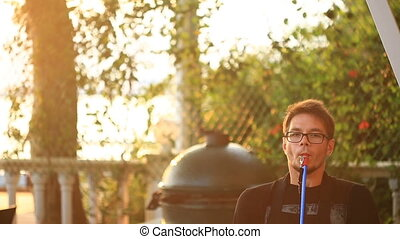 Young intelligent man smoking hookah. In an open-air...