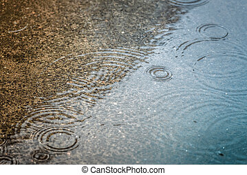 Rain drops rippling in a puddle with blue sky reflection.