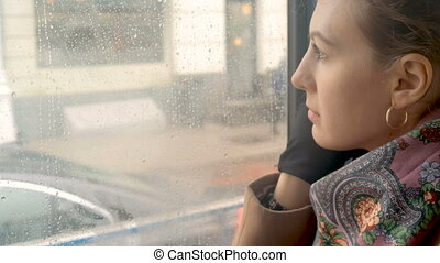 A sad girl rides a tram and looks out the window close-up -...