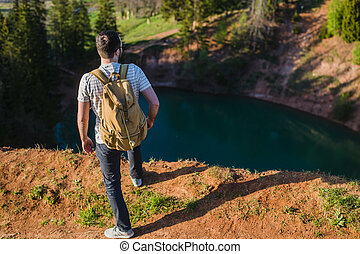 Guy standing on the cliff above the lake with the sky reflecting in it