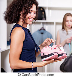 Portrait of smiling young woman holding a pair of new pink...