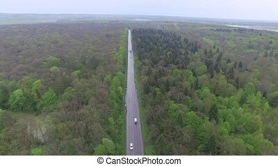 Flying over through small road with cars in green forest,...