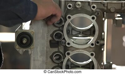 Engine manufacturing process. Hands of male worker. Adjust...