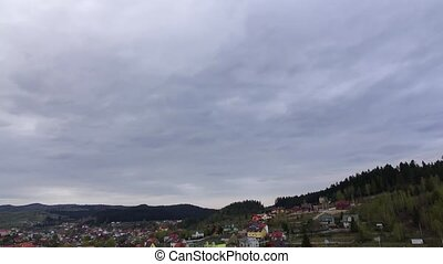 Gray rainy sky over small village on hillside. Time lapse