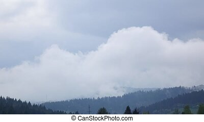 Clouds form over forest on slopes of hills, time lapse -...