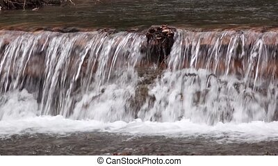 Small waterfall of clean calm mountain river with wooded...