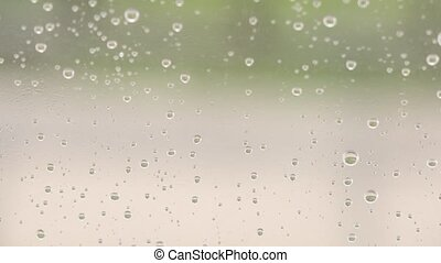 Water drops of storm rain on window with strong wind, large...