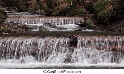 Water cascades down rocky steps among mosses and spring...
